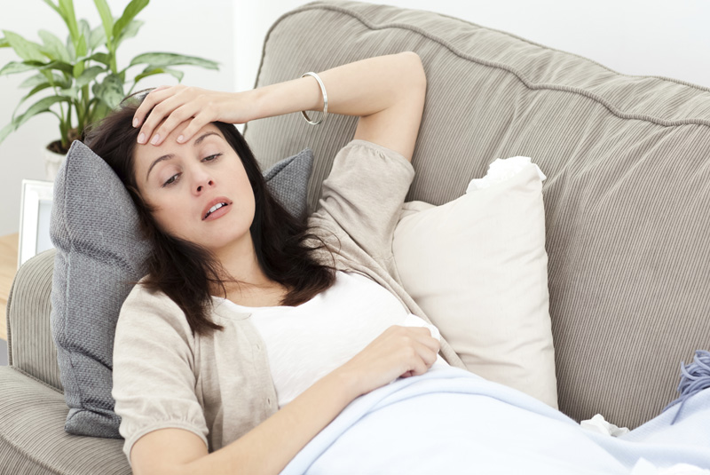 Indisposed woman feeling her temperature while resting on the so