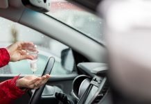 woman using hand sanitizer while sitting in car