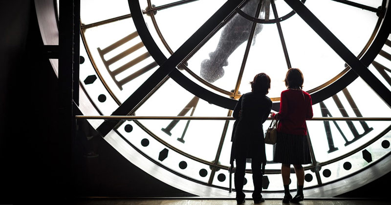 Women Standing Near Townhouse Clock | Does Time Pass Faster As You Get Older