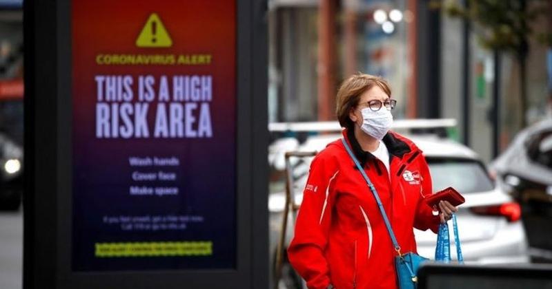 A woman walking past a billboard about covid 19 alert | Coronavirus New Strains Wreaking Havoc In Europe