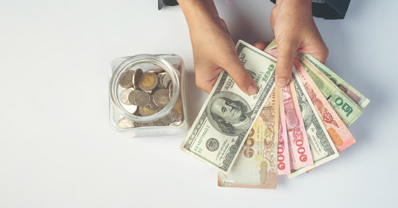 person counting dollars | How To Save Money