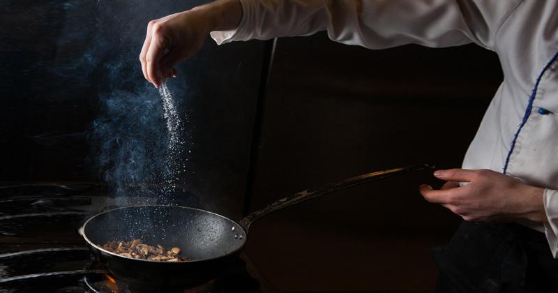 Chef sprinkling salt on sautéed mushroom | Types of Salt