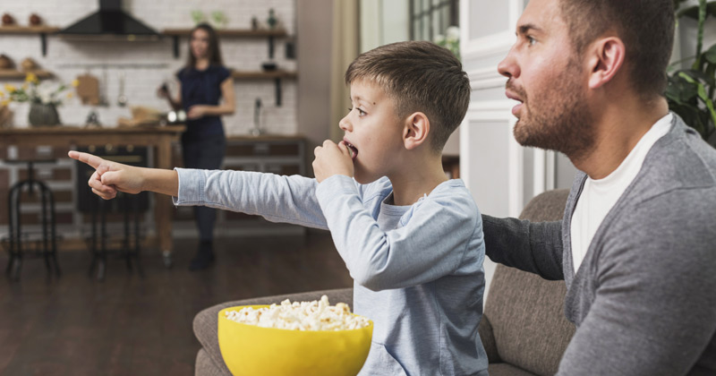 Father and Son watching movie while eating popcorn | Best Father's Day Movies