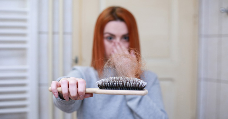 A Woman Showing her broken hair strands on a comb | Hair Loss Prevention Tips